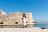 Happy tourist girl on holiday trip to Heraklion, Crete, Greece. Young woman traveller enjoyes sunshine sitting on the dock of Heraklion Venetian port marina. Venetian fort at background. - 231972867