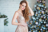 Holidays, celebration and people concept - young woman in elegant dress over christmas interior background