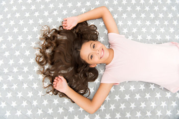 Girl child with long hair lay on bed top view. Child curly hairstyle relaxing. Conditioner mask organic oil keep hair shiny and healthy. Amazing hair tips. Keep hair curly even next morning © Roman Stetsyk