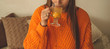 Leinwanddruck Bild - Beautiful Happy Young Woman Drinking Cup Of sea buckthorn tea. In Bed in a bright orange sweater. Closeup Portrait Of Smiling Girl