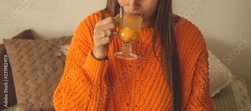 Leinwanddruck Bild Beautiful Happy Young Woman Drinking Cup Of sea buckthorn tea. In Bed in a bright orange sweater. Closeup Portrait Of Smiling Girl