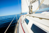 White yacht sails in the Baltic sea on a sunny day. A view from the deck to the bow and sails. Latvia - 231985650