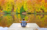 Woman meditating outdoors in the autumn park near forest lake. - 231994235