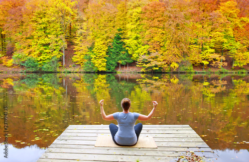 Poster Woman meditating outdoors in the autumn park near forest lake.