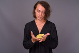 Portrait of young man holding poo in his hand - 231994450