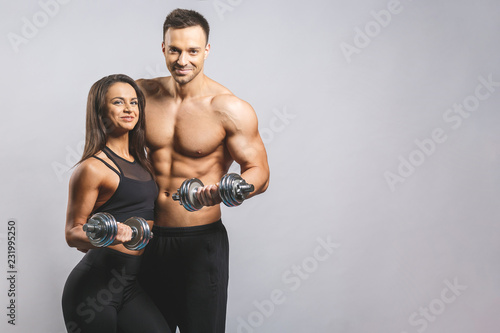 Wall mural Athletic man and woman with a dumbells isolated over white background. Personal fitness instructor. Personal training.