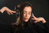 Beautiful enjoying young woman listening the music in wireless headphone with closed eyes on dark black background. Closeup - 232021005