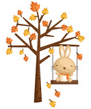 a rabbit playing in the swing on a tree - 232029031