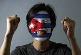 Cheerful portrait of a man with the flag of the Cuba painted on his face on grey background. The concept of sport or nationalism.