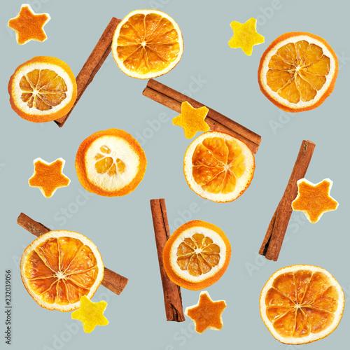 Bożenarodzeniowy tło wysuszone pomarańcze, pomarańczowa łupa w formie gwiazdy z cynamonem i. Bezszwowe tło