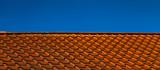 Rotes Ziegeldach mit blauem Himmel - 232041027