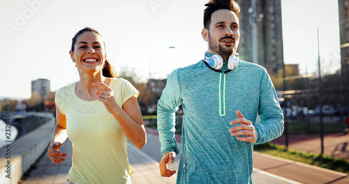 Sticker Young attractive couple running outside on sunny day