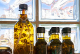 Bottles with olive oil and plant sprigs inside against the window