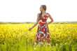Blode girl posing in red dress in yellow field