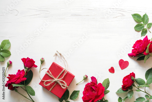Red roses flowers, gift red box with a bow and hearts on a white wooden background, copy space, top view. Festive romantic background for Valentine's Day