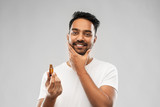 grooming and people concept - smiling young indian man applying lotion or beard oil over gray background