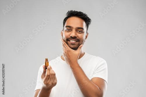 przygotowywać i ludzie pojęć - uśmiechnięty młody indyjski mężczyzna stosuje płukankę lub broda olej nad szarym tłem