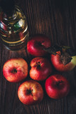 Close-up of red apples and oil in a bottle on wooden table low key