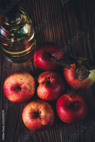 Foto Murales Close-up of red apples and oil in a bottle on wooden table low key