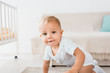 adorable toddler looking at camera on white room background
