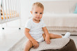 adorable toddler sitting on bean bag chair and looking at camera indoors in nursery room