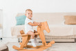 adorable smiling toddler sitting on toy wooden horse