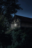 Historic house with illuminated window in forest. - 232063095