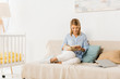 smiling adult woman sitting on couch reading book