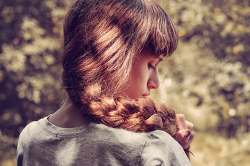 Young beautiful woman with nice braid hairstyle on nature © Julia
