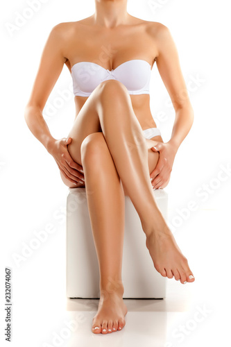 Leinwanddruck Bild Sitting woman posing in lingerie on white background