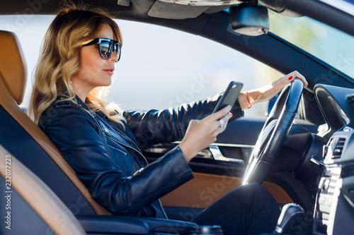Leinwandbild Motiv Photo of side blonde in black glasses with cell phone sitting in car