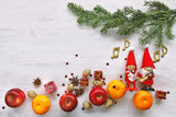 Singing gnome with apples, mandarin, gifts under christmas tree - 232077848