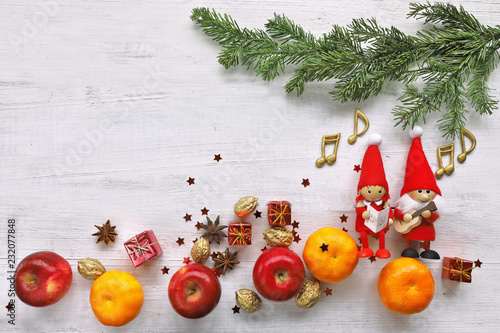 Singing gnome with apples, mandarin, gifts under christmas tree