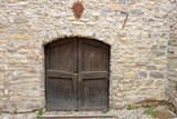 Closed the arched wooden door in a wall made of pieces of rock stones. Unused entrance of the ancient fortress in an Italian city - 232081081