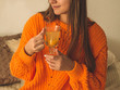 Leinwanddruck Bild - Beautiful Happy Young Woman Drinking Cup Of Coffee Or Tea. In Bed in a bright orange sweater. Closeup Portrait Of Smiling Girl