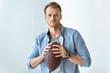 confident handsome man holding rugby ball and looking at camera near wall