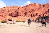 Tourists ride on donkeys in Petra, Jordan - 232094445