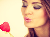 Flirty woman holding red wooden heart on stick - 232098017