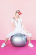 attractive female athlete in visor hat sitting on grey fitness ball and looking at camera on pink