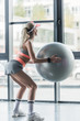rear view of sporty girl in visor hat exercising with fitness ball at gym