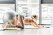 rear view of female athlete doing exercise on fitness mat at sports hall