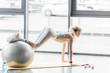 rear view of sportswoman doing exercise with fitness ball at gym