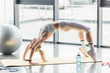 selective focus of young sportswoman doing bridge exercise on fitness mat at gym