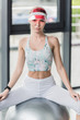 attractive female athlete in visor hat posing on grey fitness ball at gym