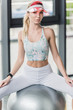 young beautiful sportswoman in visor hat sitting on grey fitness ball at gym