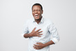 Handsome african man laughing out loud at funny meme or joke he found on internet, smiling broadly.