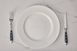 empty plate with fork and knife on white marble background