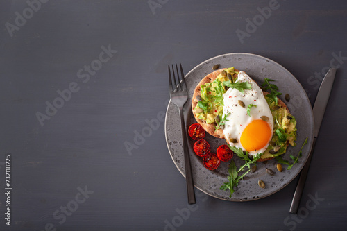 Leinwanddruck Bild breakfast avocado sandwich with fried egg and tomato