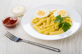 Pasta with boiled eggs, parsley in plate, mayonnaise and ketchup