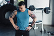 young asian sportsman with hands on hips at gym